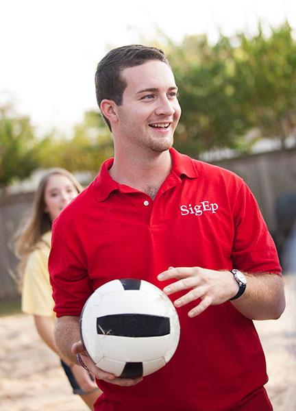 Male student holding volleyball