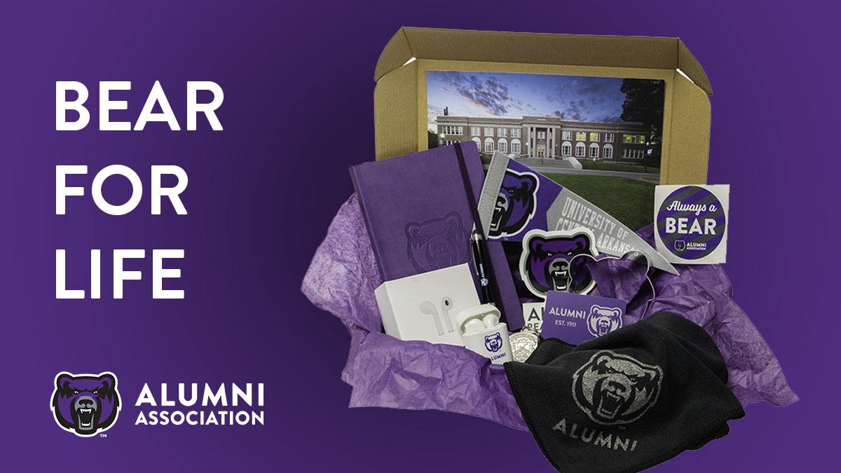 Purple background with white wording saying Bear for Life followed by UCA Bear Head alumni logo. On the right side is a box filled with UCA alumni branded items.
