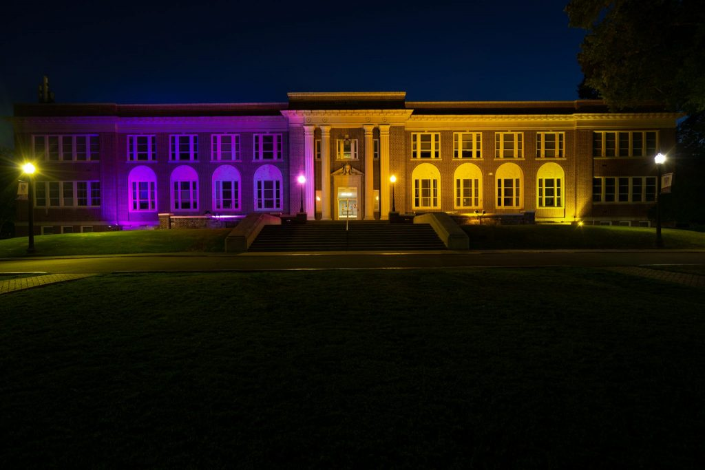 Picture of Old Main on UCA's campus, lit in purple and gold