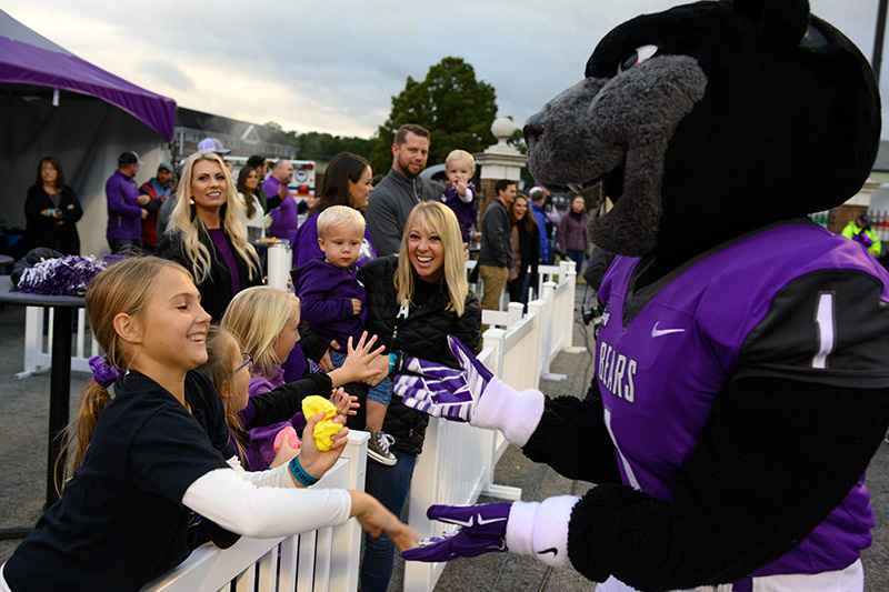 UCA mascot Bruce D. Bear greets children (from left) Oliva Gardner, Amelia Gardner, Henleigh Russell and Ben Russell, who is being held by Erica Russell '05, '09, on game day. Behind them, Ashley Gardner '06, '07 looks on, as well as Melia Hill '05, '07, Zach Hill and Hayden Hill.