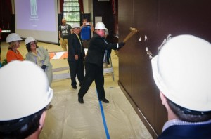 UCA President Tom Courtway swings a golden sledgehammer to topple a wall during UCA's 'wall crashing' event on June 9 while other UCA guests and dignitaries look on.