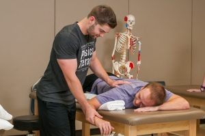 Student applying shoulder technique to another student on a treatment table