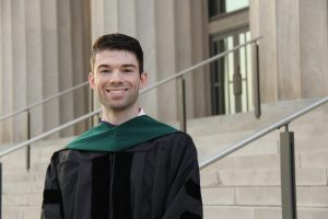 picture of graduate on steps with regalia