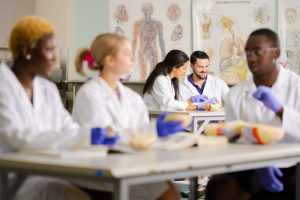 Students in lab coats and gloves at anatomy table