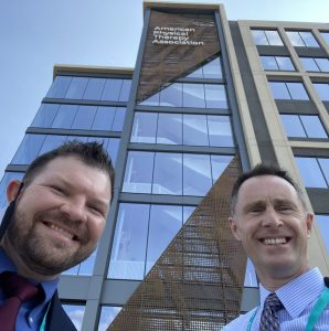 Drs. Tipton and Garrison standing outside in front of new building for APTA Headquarters.
