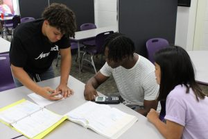 Three students in tutoring services center working problems together