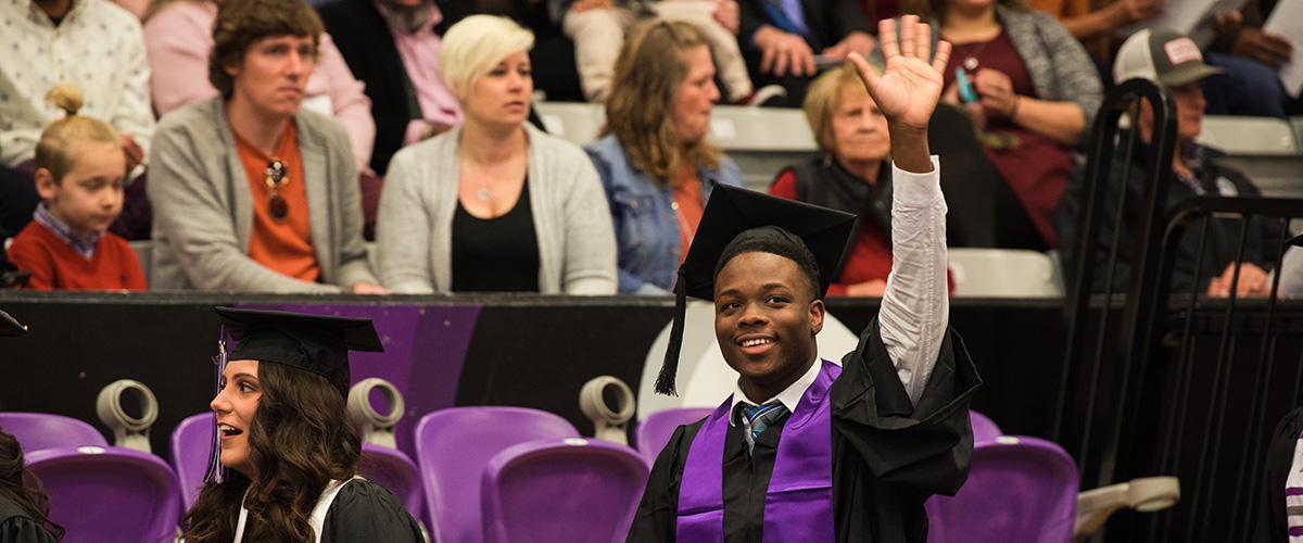 Student waving at commencement